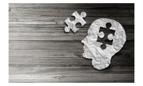 Picture of a paper head laying flat on a table with a missing puzzle piece. Coconut oil and the brain?