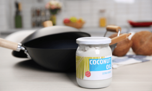 Picture of extra virgin coconut oil in a jar on the kitchen counter with a wok.