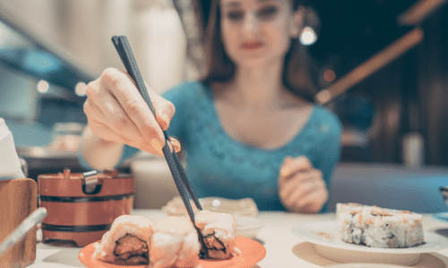 Picture of a woman with chopsticks eating sushi at a restaurant. Eating out on a renal diet: tips & tricks.