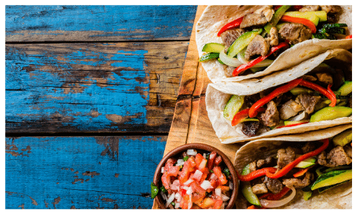 Picture of beef and vegetable fajitas on a wood platter with a small bowl of salsa on top a blue wooden table top.