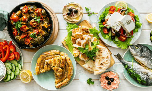 Colorful picture of different staple Greek foods on top a white wood table top.