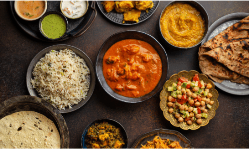 Picture of colorful Indian dishes on top a brown table top.