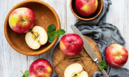 Picture of whole and sliced apples in wooden bowls on a table. Kidney superfoods.