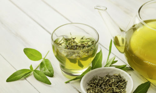 Picture of green tea leaves and a glass cup and pot full of green tea. Kidney superfoods.