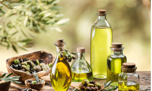 Picture of olive oil in glass jars with olives, and olive leaves on a wood table outside. Kidney superfoods.
