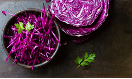 Picture of sliced and shredded red cabbage in a bowl on top of a brown table. Kidney superfoods.