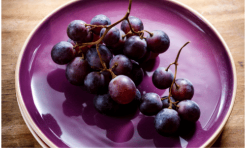 Picture of red grapes on a purple plate. Kidney superfoods.