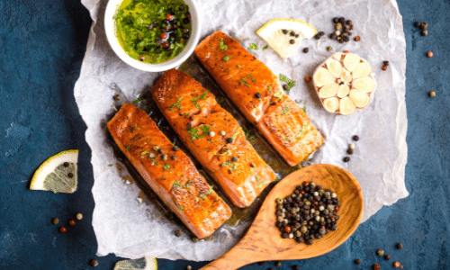 Picture of cooked salmon fillets with seasonings on blue rustic concrete background. Kidney superfoods.