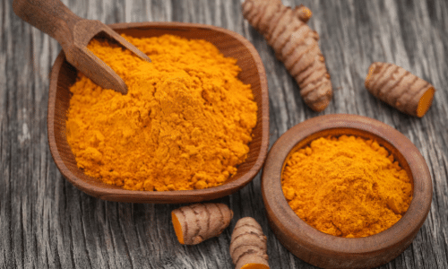 Picture of raw turmeric and powder in wooden bowl. Kidney superfoods.