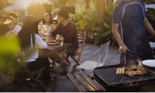 Picture of friends eating and drinking at an outdoor barbecue.