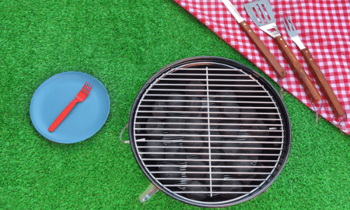Picture of red checkered table cloth with utensils, plate, and a grill on green turf. Top Summer Tips For Dialysis Patients.